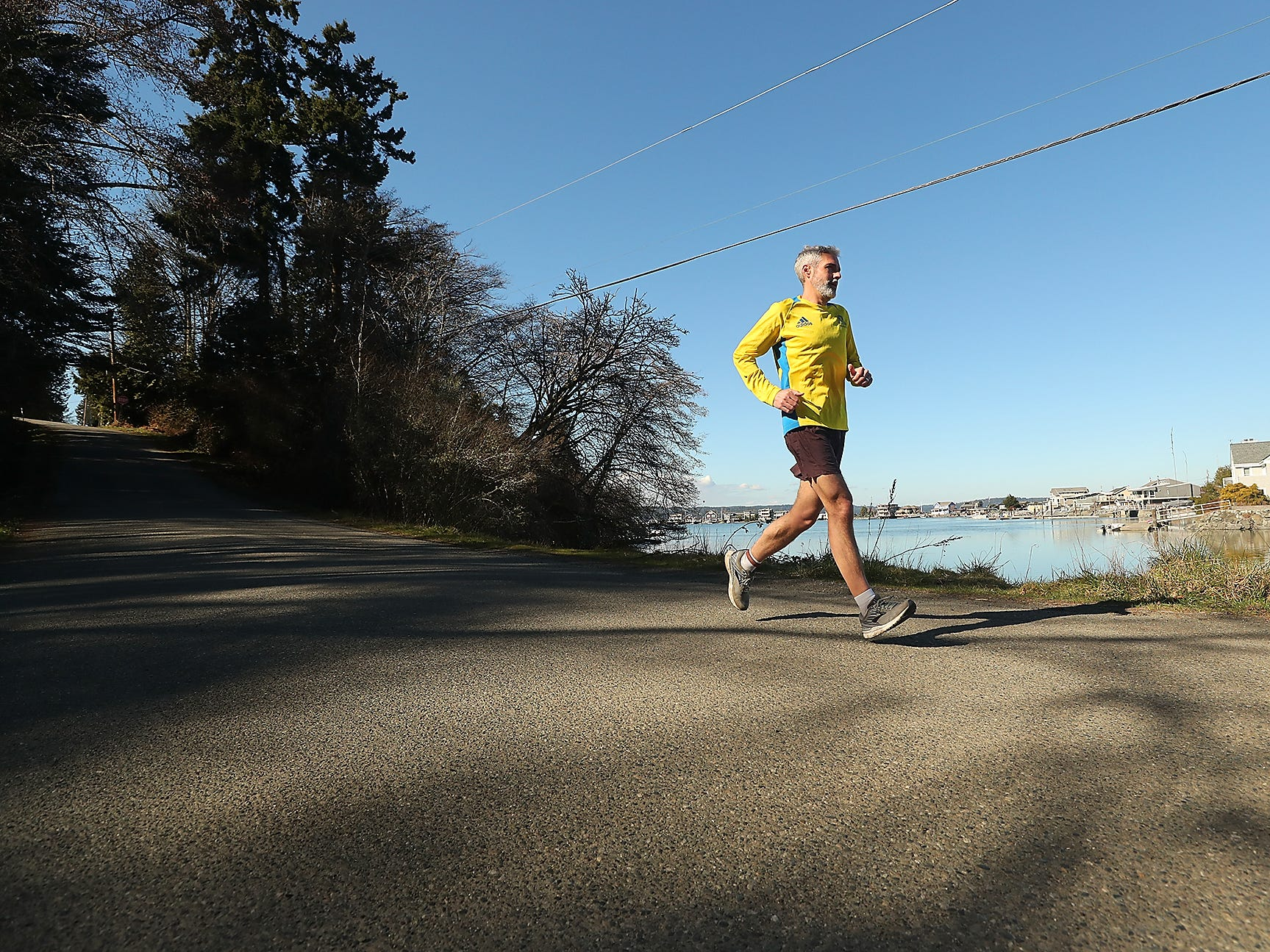 Peter Vosshall runs down Bainbridge Island's Point Monroe Drive on Friday, March 1, 2019. Vosshall has made it his goal this year to run every street on the island.