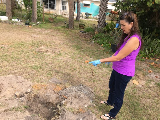 Sandra Sullivan, of South Patrick Shores, points to a hole in her yard where EPA sampling was halted because debris was found. Sullivan said the EPA unearthed a variety of debris, including what looked like a military green piece of airplane aluminum.