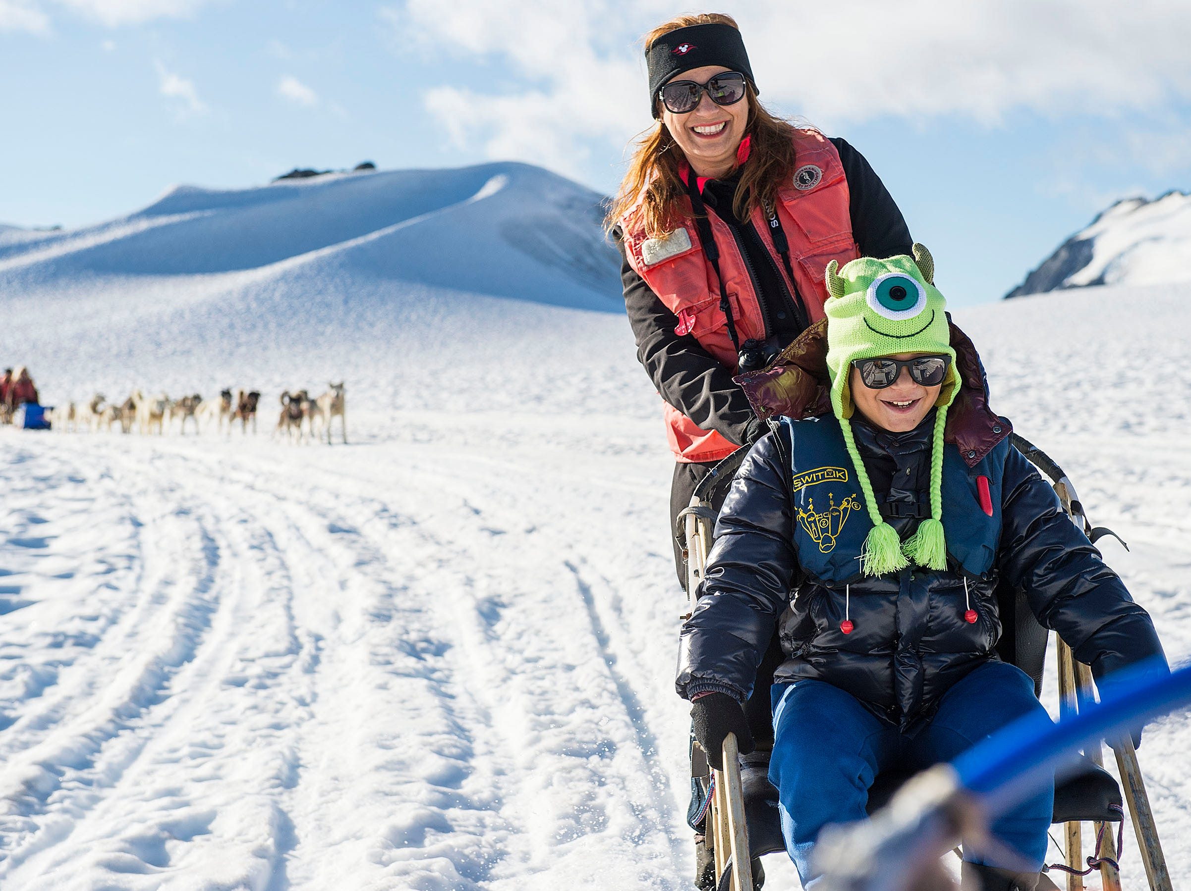 As part of the Alaska itinerary, Disney Cruise Line guests explore Musher's Camp at the Klondike Gold Rush National Historic Park in Skagway. Guests meet the mushers and sled dogs and are whisked on a thrilling ride through Alaska's temperate rainforest by the husky team.