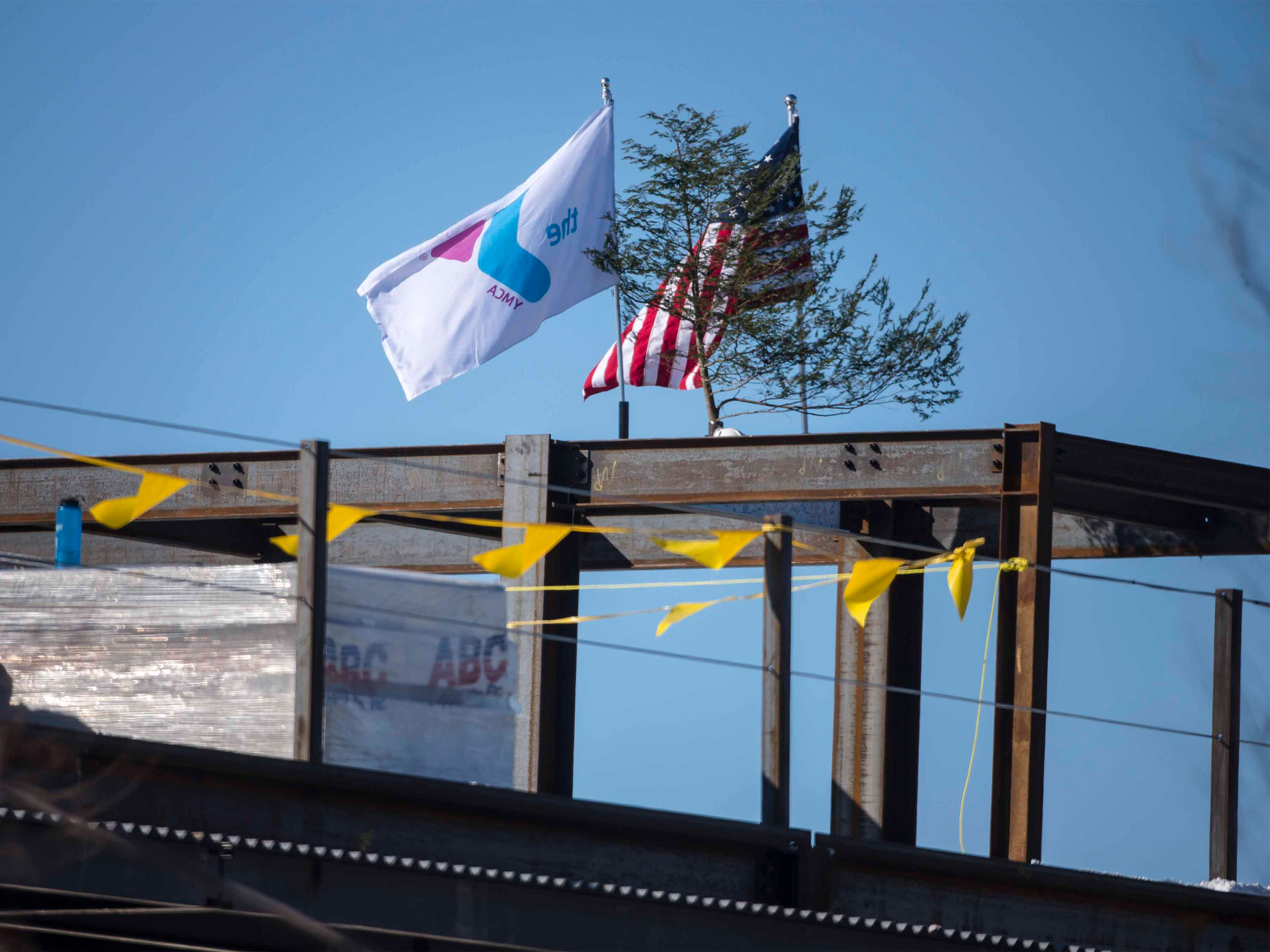 """The YMCA flag joins the American flag and an evergreen cutting atop the new Burlington YMCA building after a """"topping off"""" ceremony Thursday, Feb. 28, 2019."""