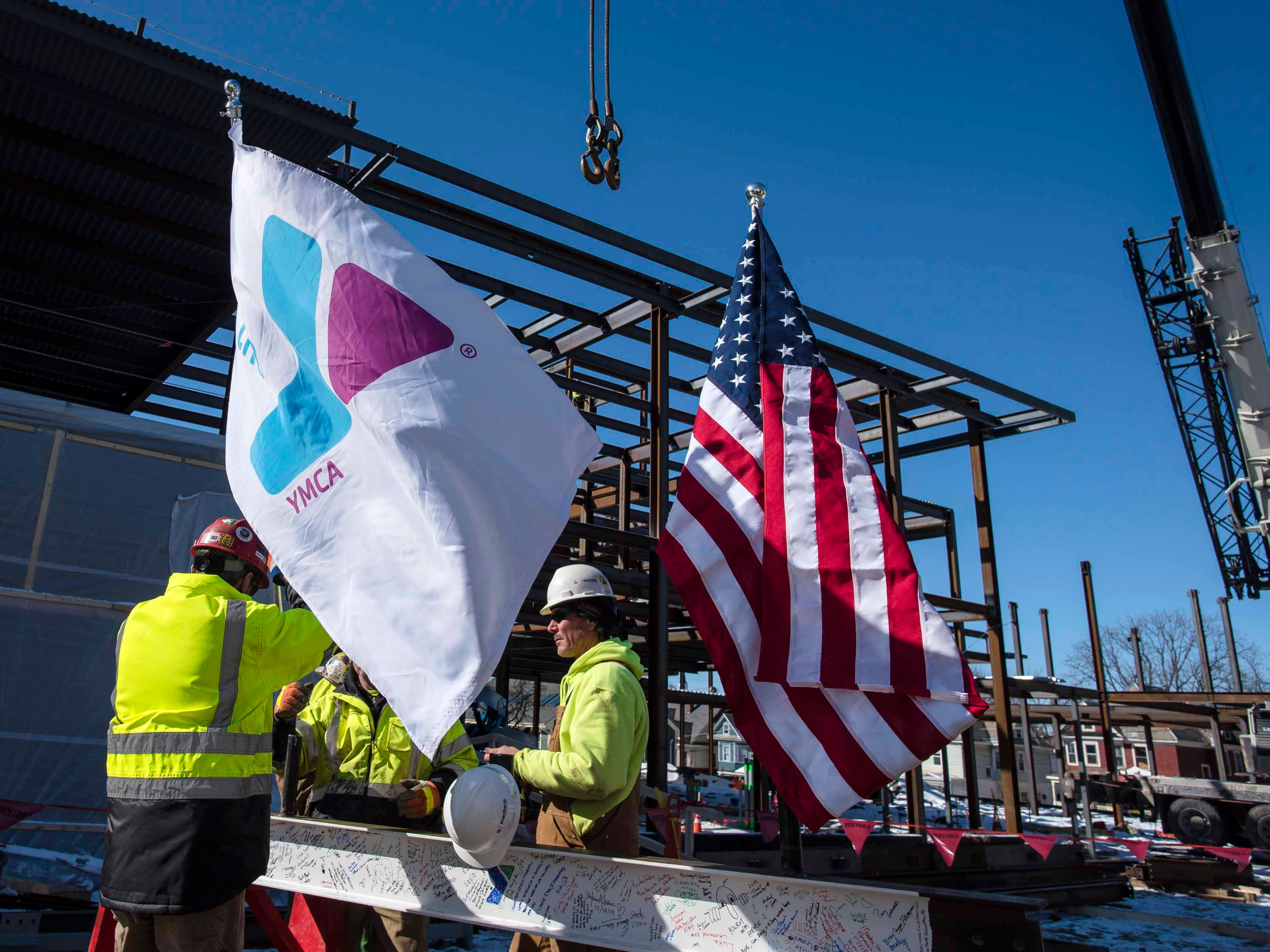 """Construction workers place a YMCA flag on a beam about to be placed atop the new Burlington YMCA building during a """"topping off"""" ceremony Thursday, Feb. 28, 2019."""