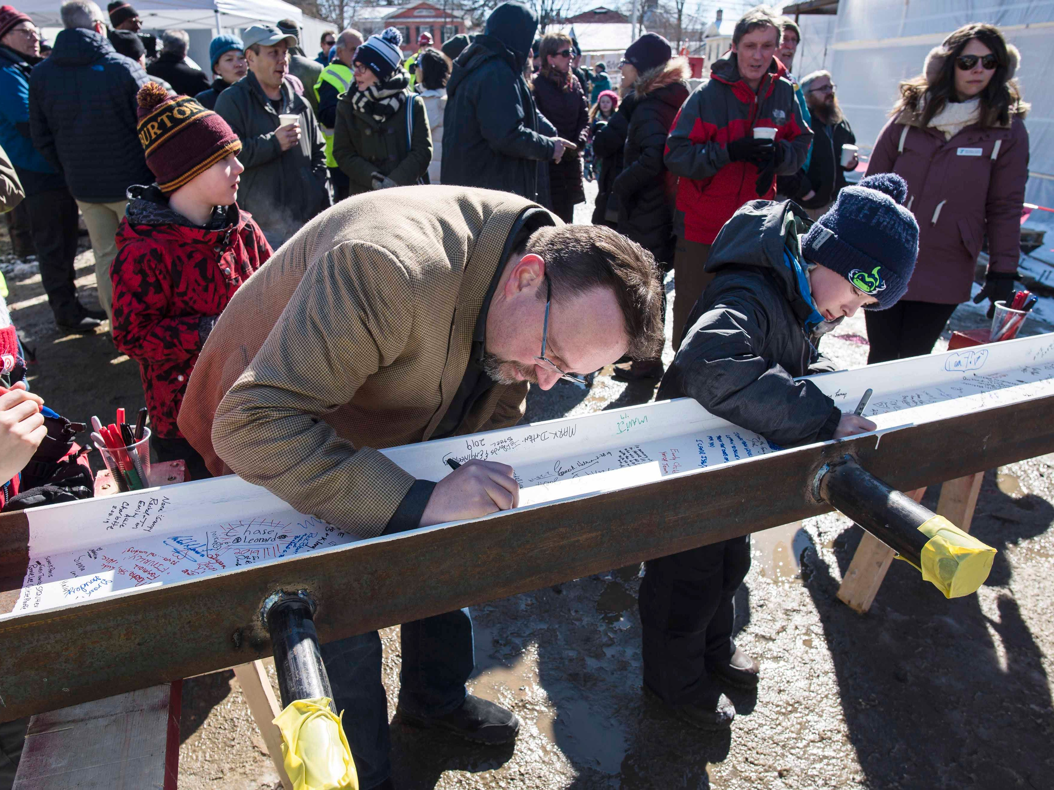 """Paul Simon of Etna, New Hampshire, center, was among the people who signed a beam about to be placed atop the new Burlington YMCA building during a """"topping off"""" ceremony Thursday, Feb. 28, 2019."""