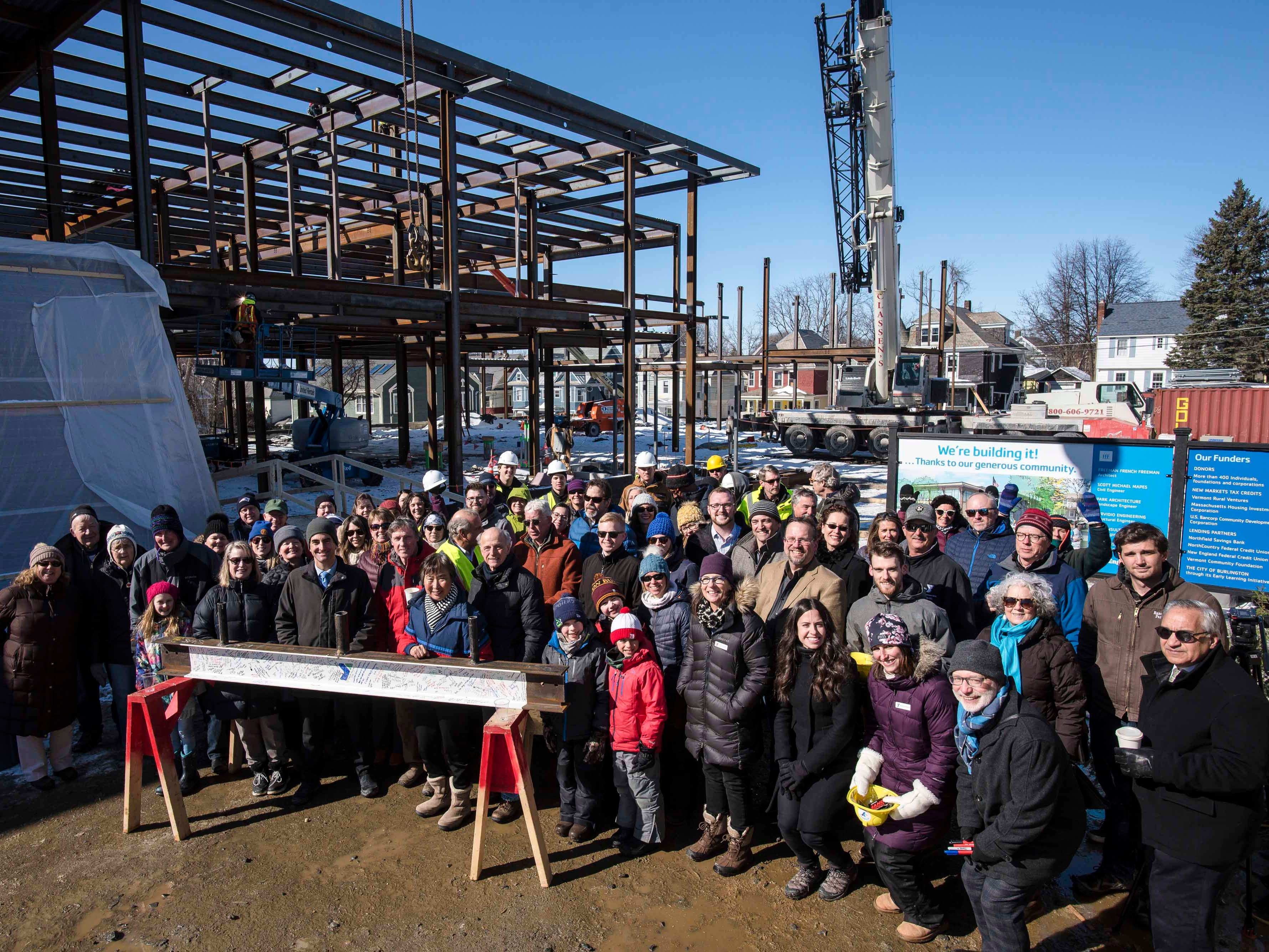 """Community members gather during a """"topping off"""" ceremony for the new Burlington YMCA building Thursday, Feb. 28, 2019."""