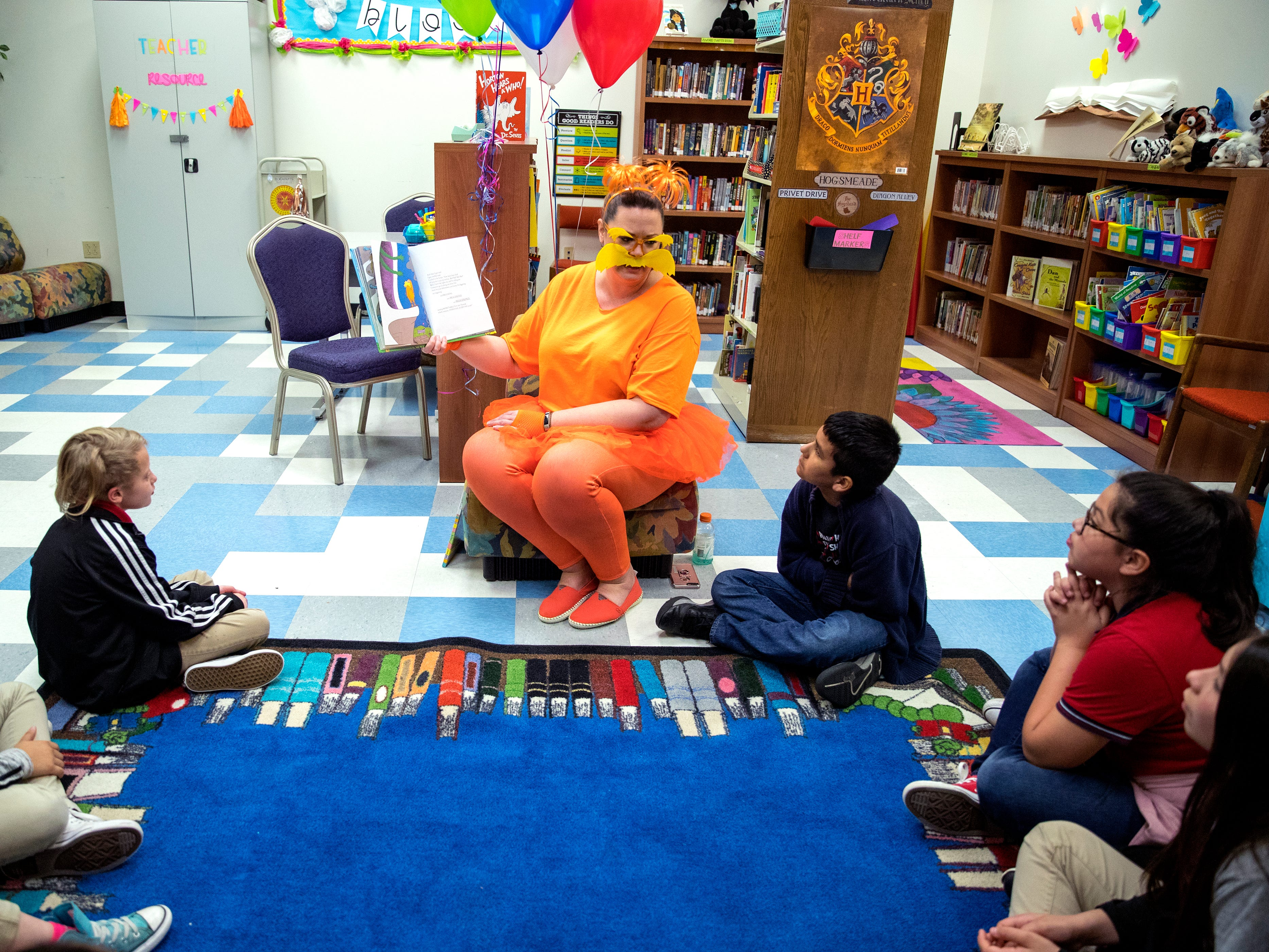 "School of Science and Technology librarian Tara Reed reads ""The Lorax"" to students during a Dr. Seuss's Birthday and Read Across America event on Friday, March 1, 2019. Students later read to a dog that visited from the Gulf  Coast Humane Society."