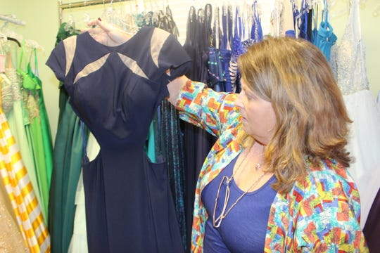 Wedding Belles owner Lisa Forest displays one of this season's hot styles, jersey gowns with cut-outs.
