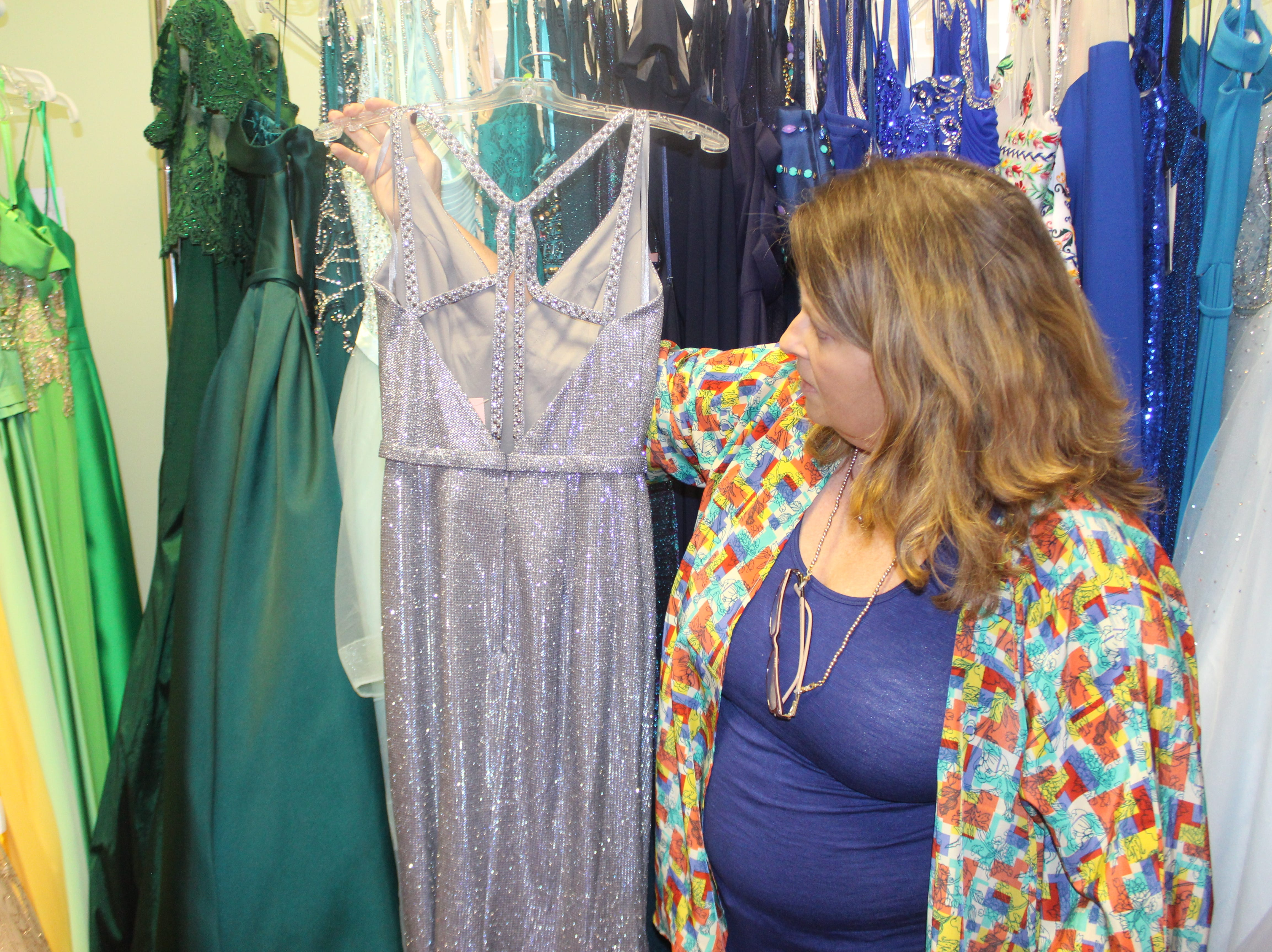 Wedding Belles owner Lisa Forest shows off one prom gown trend, a metallic jersey gown featuring a strappy back.