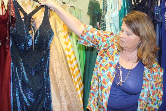 Wedding Belles owner Lisa Forest shows  off one of the hot dresses of this year's prom season, a jersey gown with a metallic sheen.