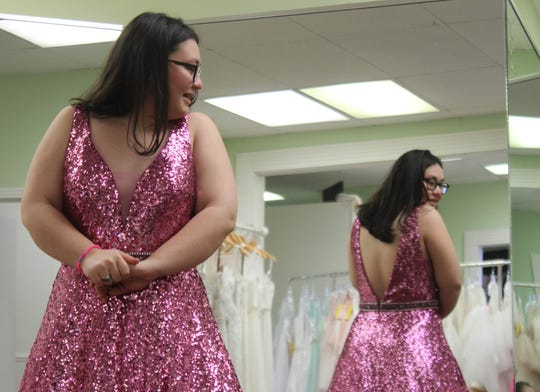 Houston County High School junior Allie Steele smiles at her reflection as she shows off her sequined prom gown at Wedding Belles in Clarksville.