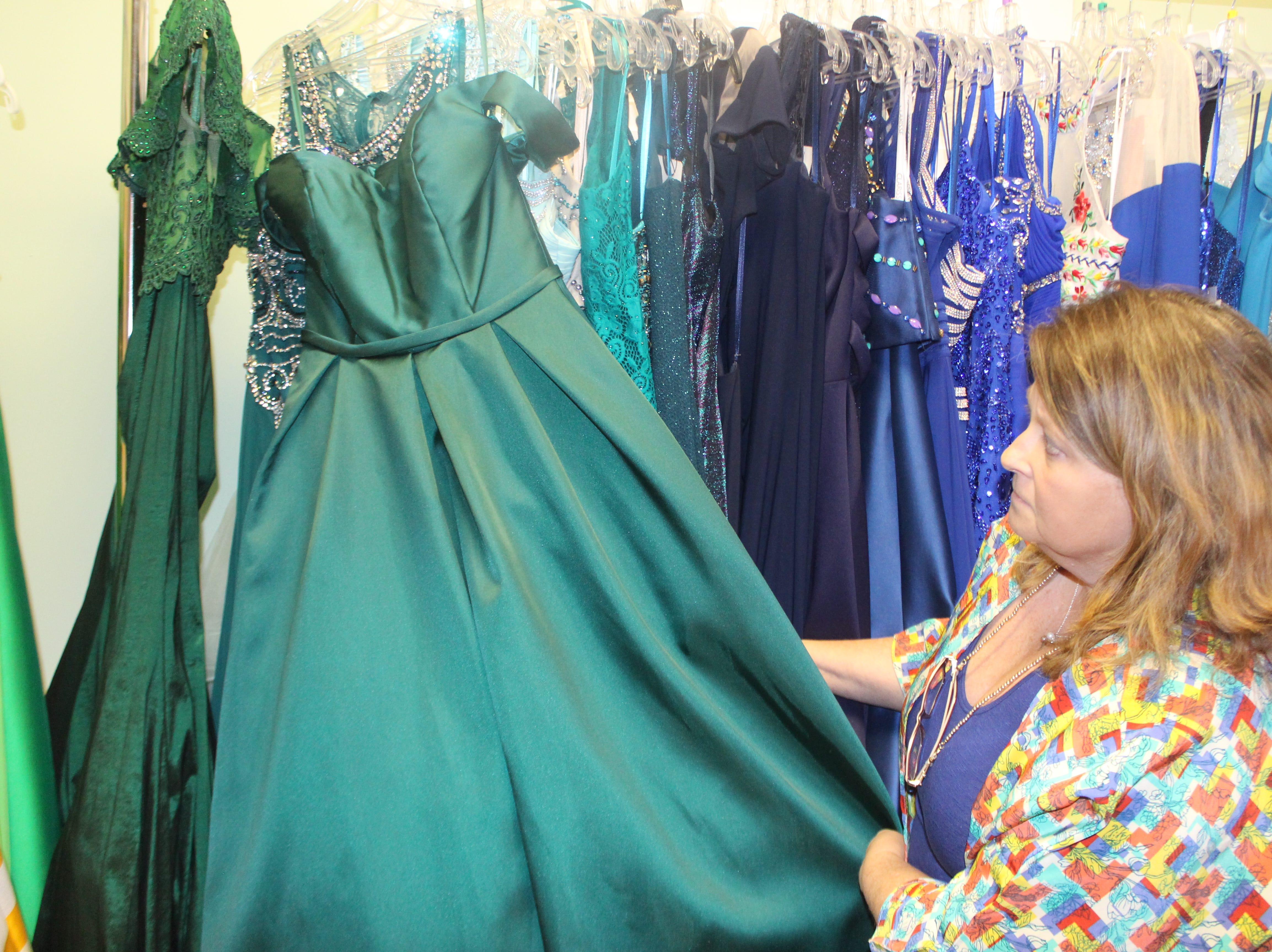 Wedding Belles owner Lisa Forest shows off a ball gown in one of the hot hues of the season, forest green.