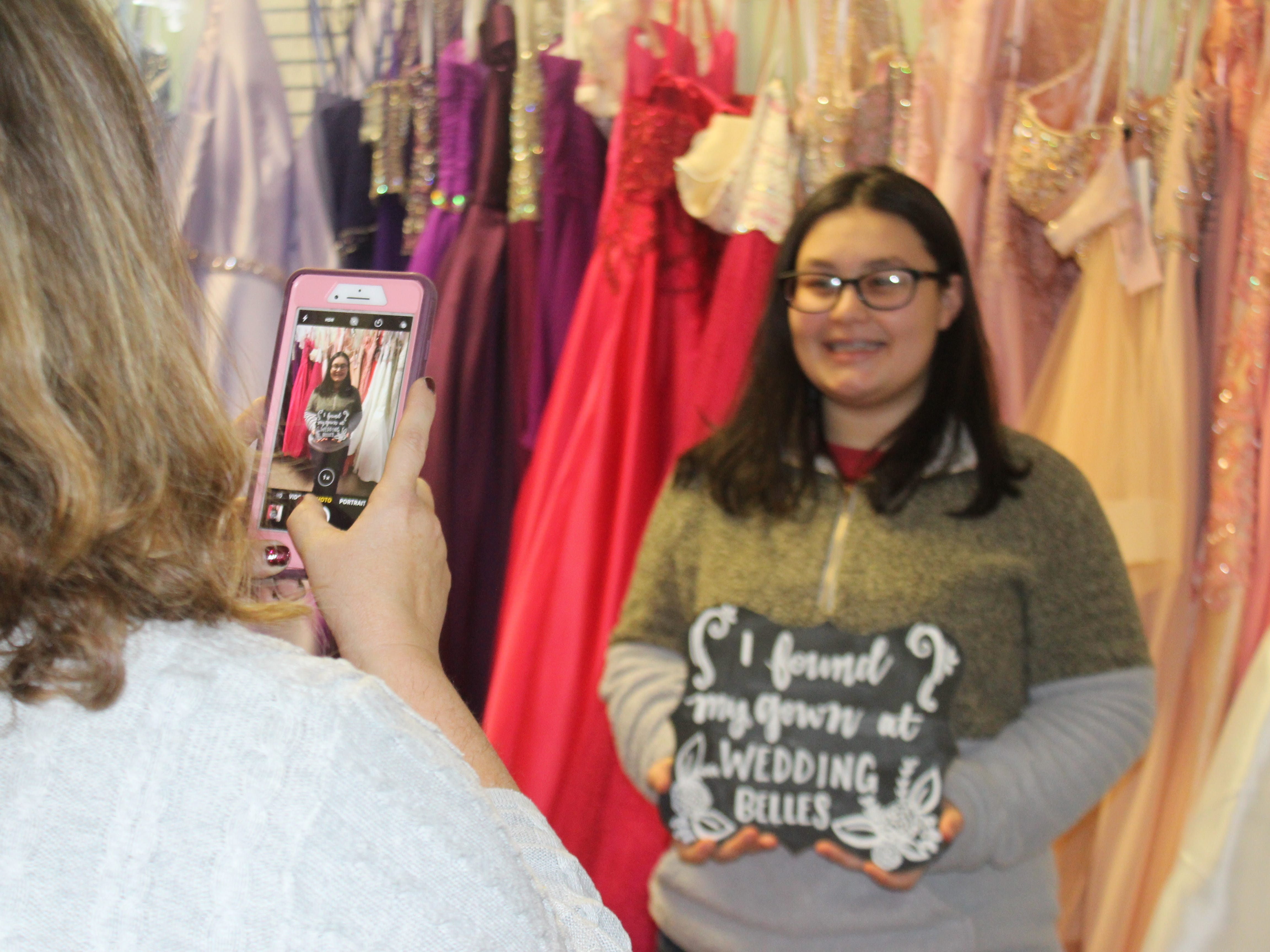 Houston County High School junior Allie Steele gets her photo taken by Wedding Belles owner Lisa Forest after she said yes to the dress.