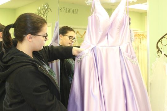 Callie Sasser, a senior at Houston County High School, shows off the pockets in the lavender ball gown she picked for the prom.