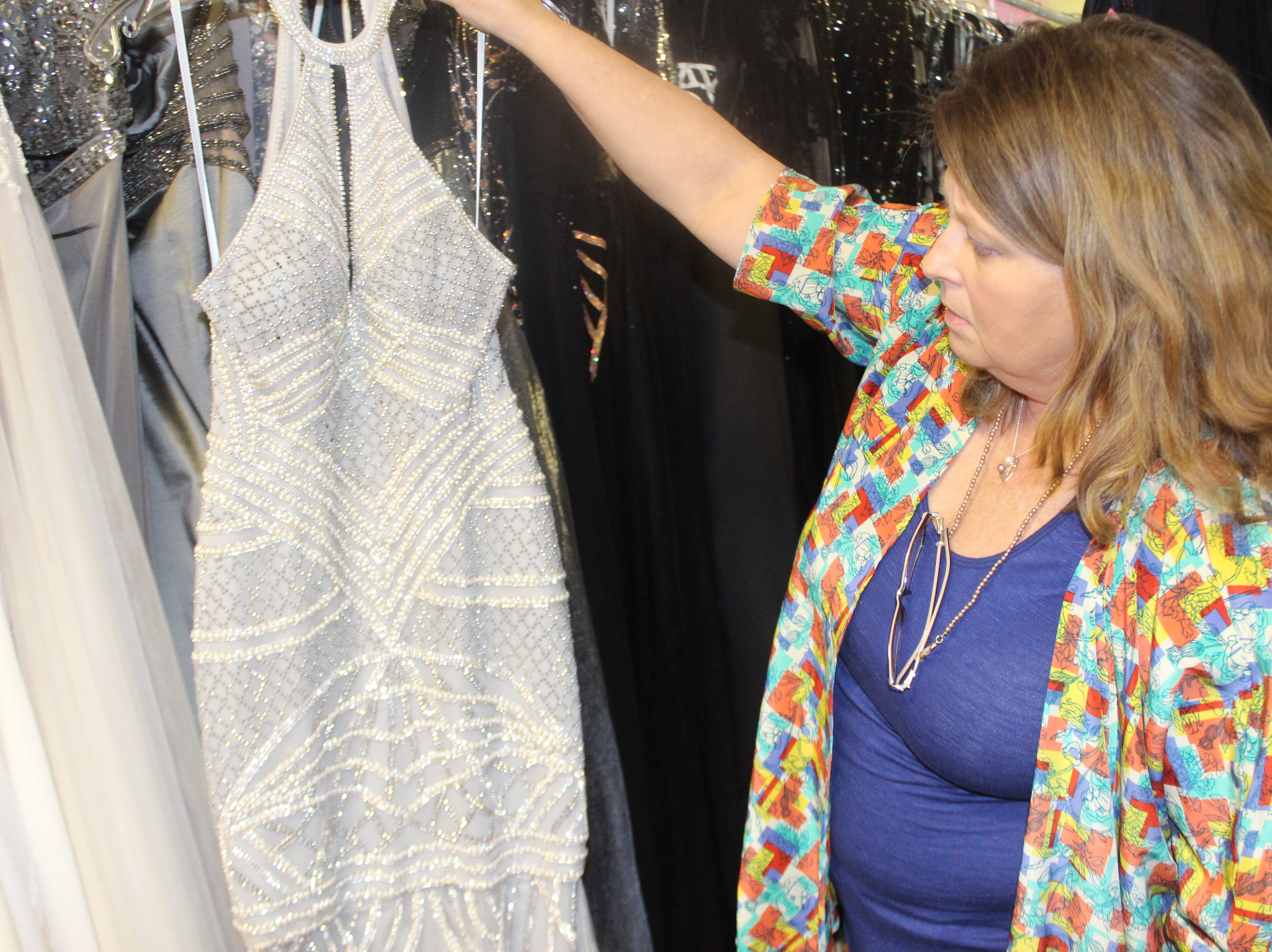 Wedding Belles owner Lisa Forest shows off a fitted beaded gown.