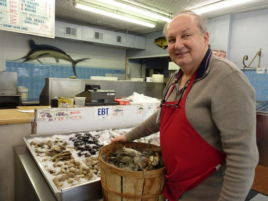 Myron Zabawsky, owner of Pete's Fish Market, with a bushel of crabs.