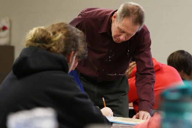 Substitute teacher Edward Finlay helps a student at River View High School on Friday.