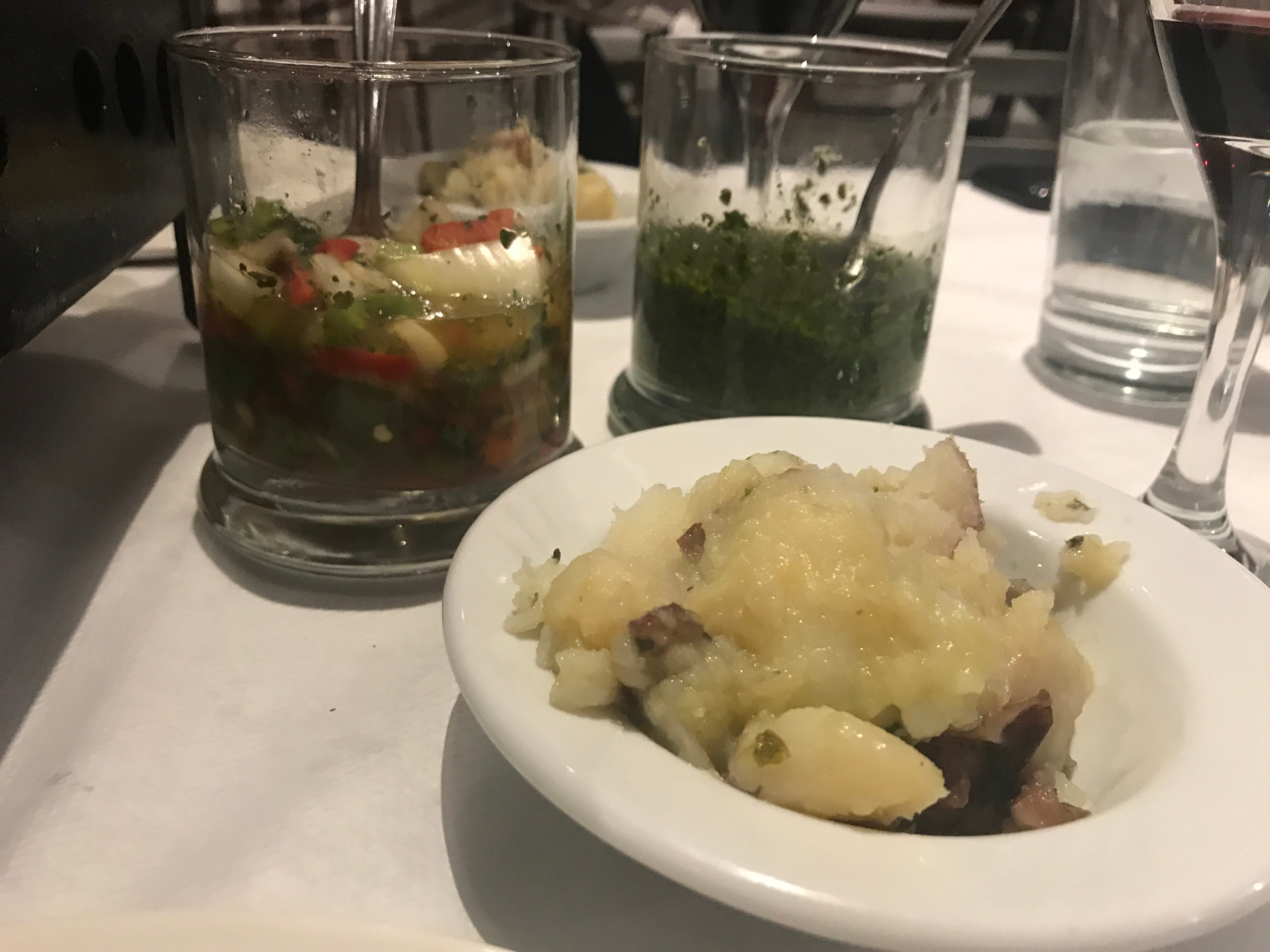 Meals are served with sides of potatoes, salsa criolla and chimichurri.