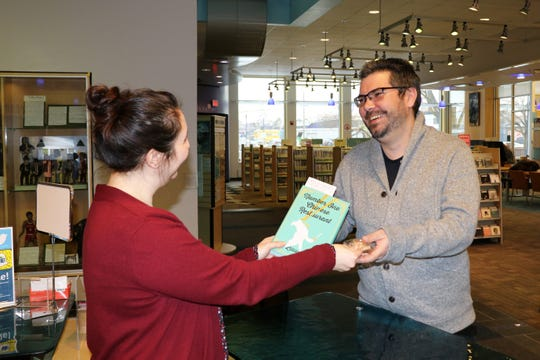 """Ferndale librarian Darlene Hellenberg gives patron Luke Grange a copy of a new novel, """"No. 1 Chinese Restaurant,"""" and a fortune cookie hyping the author's planned visit to Berkley on April 11."""
