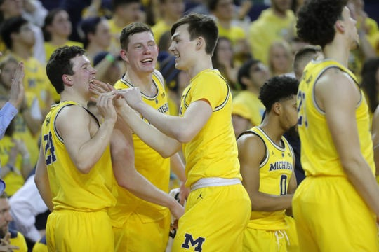 Michigan forward Colin Castleton is met by teammates after leaving the gameThursday, February 28, 2019 at the Crisler Center in Ann Arbor, Mich.
