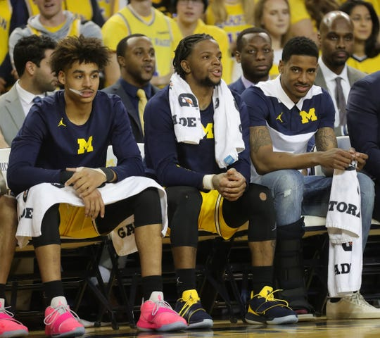 Left to right: Michigan's Jordan Poole, Zavier Simpson and Charles Matthews on the bench Thursday, Feb. 28, 2019 at Crisler Center in Ann Arbor.