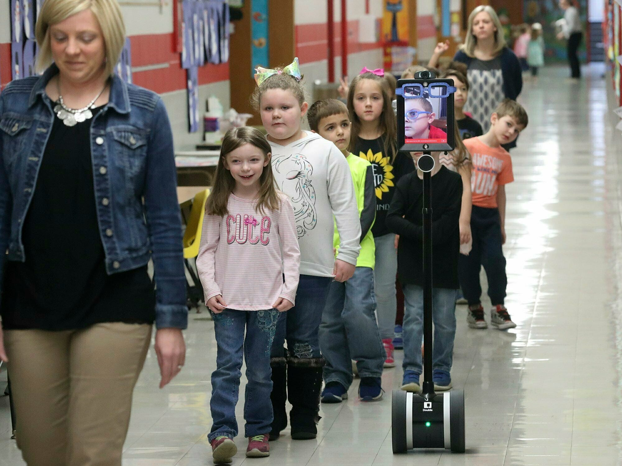 In this Thursday, Feb. 28, 2019 photo, Levi Suttles, 6, displayed on a monitor, follows his classmates down a hallway at Miami View School in South Charleston, Ohio. The robot, designed by the Ohio State University engineering department, allows the young leukemia patient to move around and interact with his class from a computer at home.