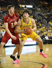 Michigan forward Brandon Johns Jr. (23), right, averaged roughly one point and one rebound in 4.1 minutes last season as a freshman.