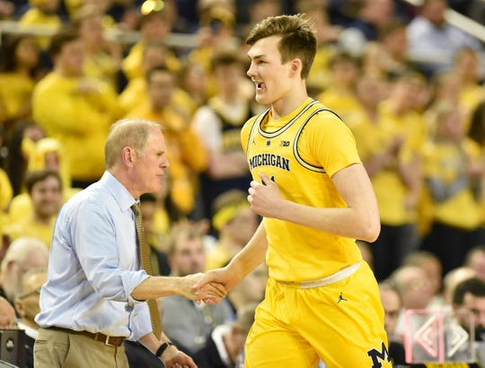 Michigan head coach John Beilein shakes hands with forward Colin Castleton (11) as he exits the game in the second half.