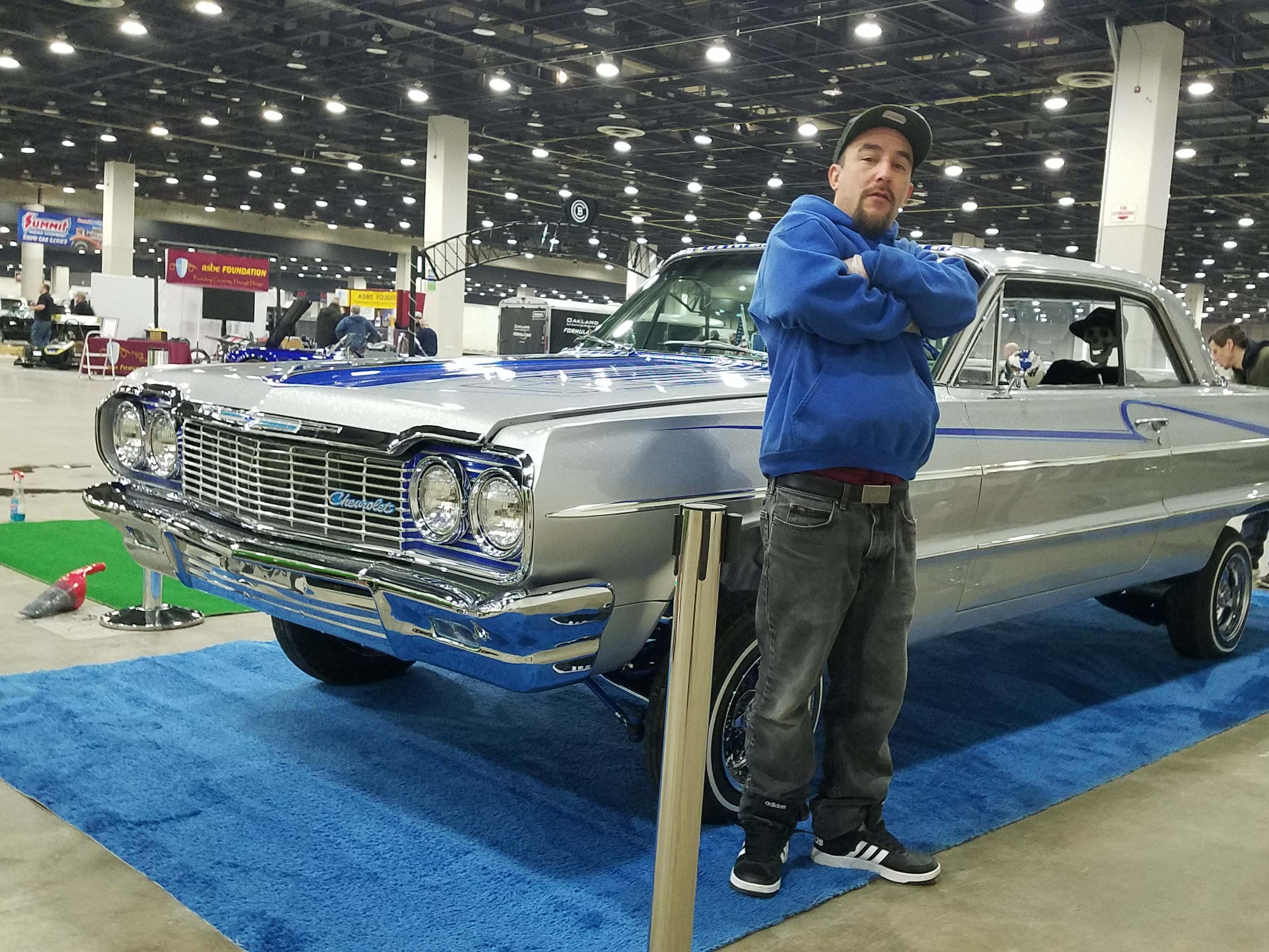 Low-rider participant Jose Madrigal of southwest Detroit shows off his 1964 Impala - stuffed with low-rider suspension and 5.7-liter Corvette V-8 engine.