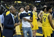 Michigan assistant coach Deandre Haynes, left, shares a moment with senior guard Charles Matthews after Matthews addresses the crowd after the game, the final home game of the season.