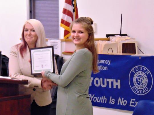 Horseheads Youth Court coordinator Holly Baumgardner, left, congratulates new member McKenzie Denson.