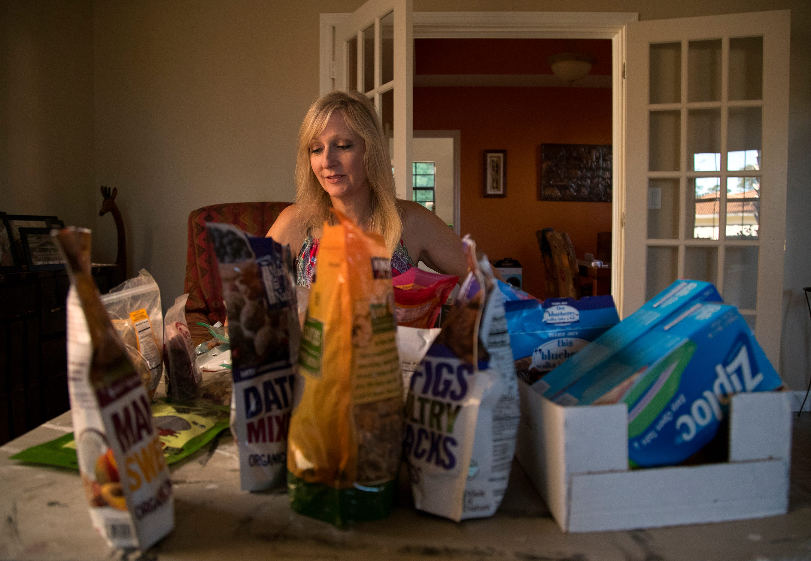 Jennifer Cecil prepares food packages on Thursday for a 300-mile kayak trip her husband Mark and stepson Maxfield Seixas are taking from Tampa to Key Largo.