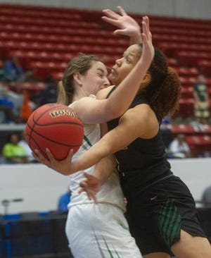 Nease's Kiya Turner collides with Fort Myers' Riley Ludlam as she goes up for a basket during the first half of their FHSAA Girls 7A semifinal game at The RP Funding Center in Lakeland Friday.
