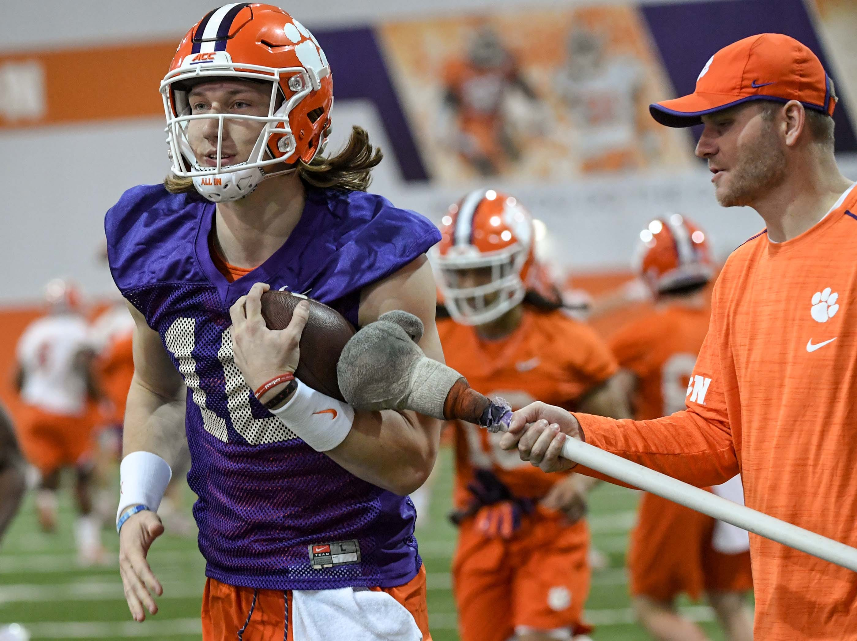 Clemson quarterback Trevor Lawrence (16) runs by Clemson quarterbacks coach Brandon Streeter during practice at the Poe Indoor Facility in Clemson Friday.