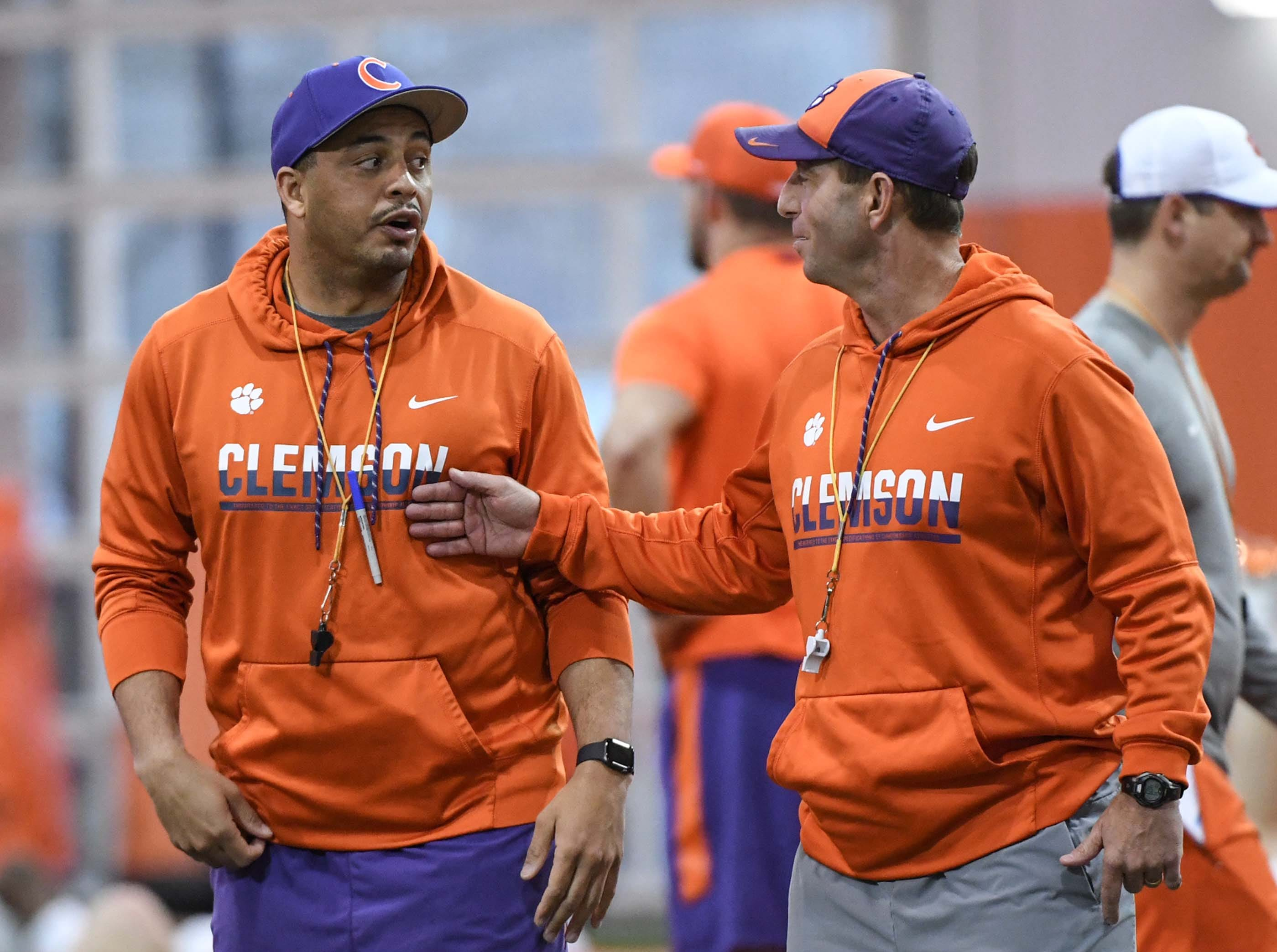 Clemson co-offensive coordinator Tony Elliott, and head coach Dabo Swinney talk during practice at the Poe Indoor Facility in Clemson Friday.