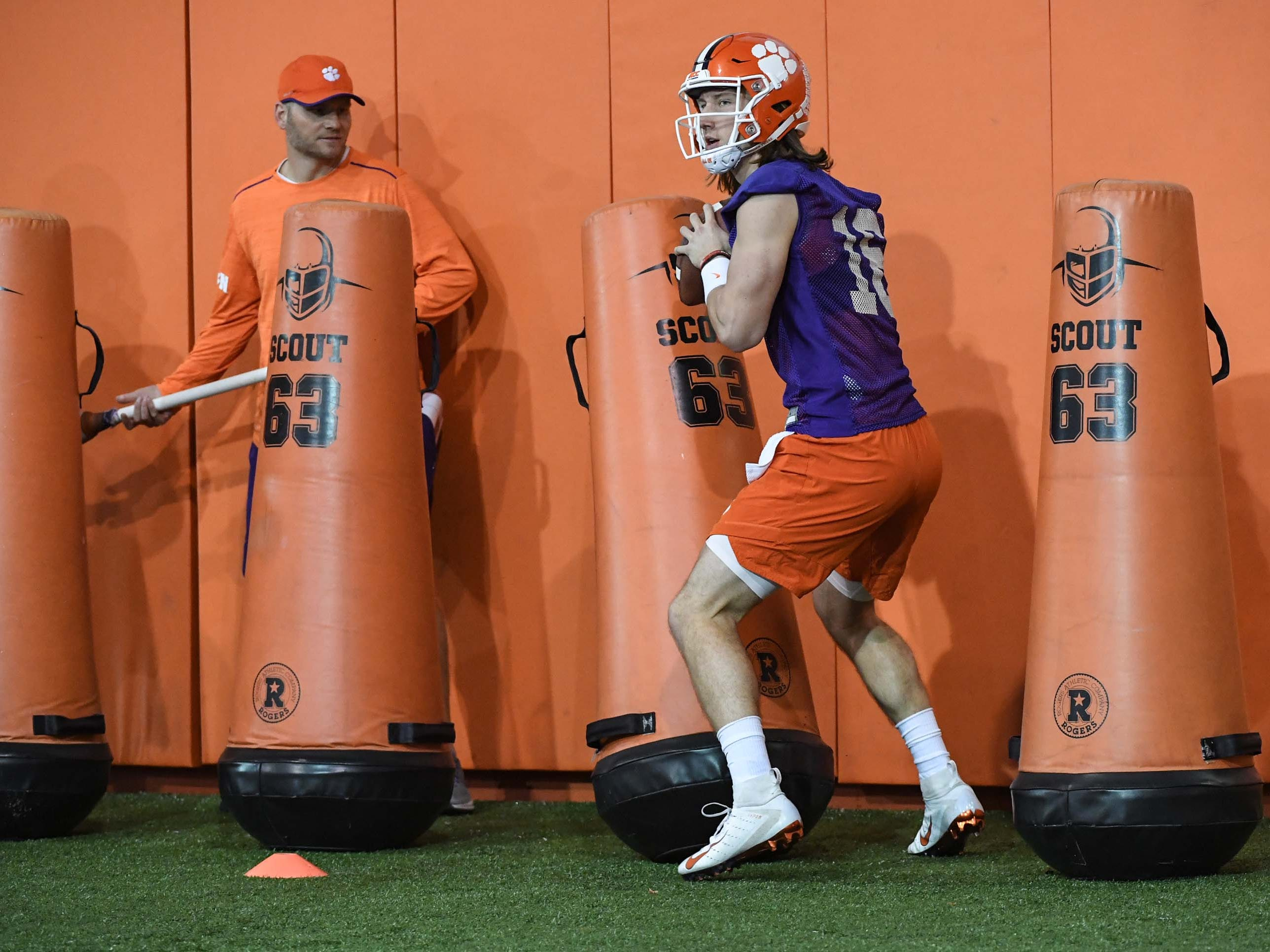 Clemson quarterback Trevor Lawrence (16) runs in a drill with quarterbacks coach Brandon Streeter, left, during practice at the Poe Indoor Facility in Clemson Friday.