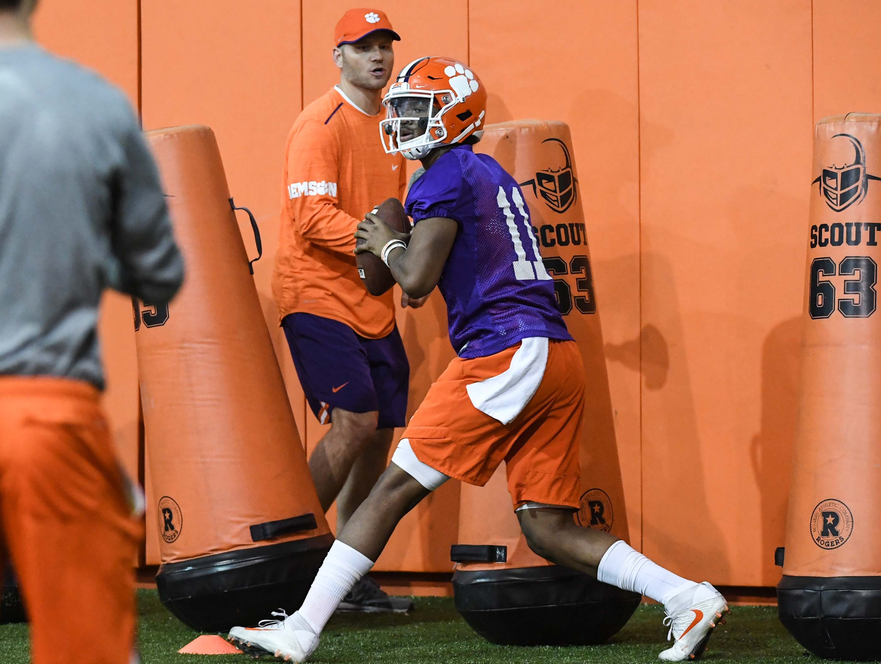 Clemson quarterback Taisun Phommachanh(11) runs in a drill with quarterbacks coach Brandon Streeter, left, during practice at the Poe Indoor Facility in Clemson Friday.