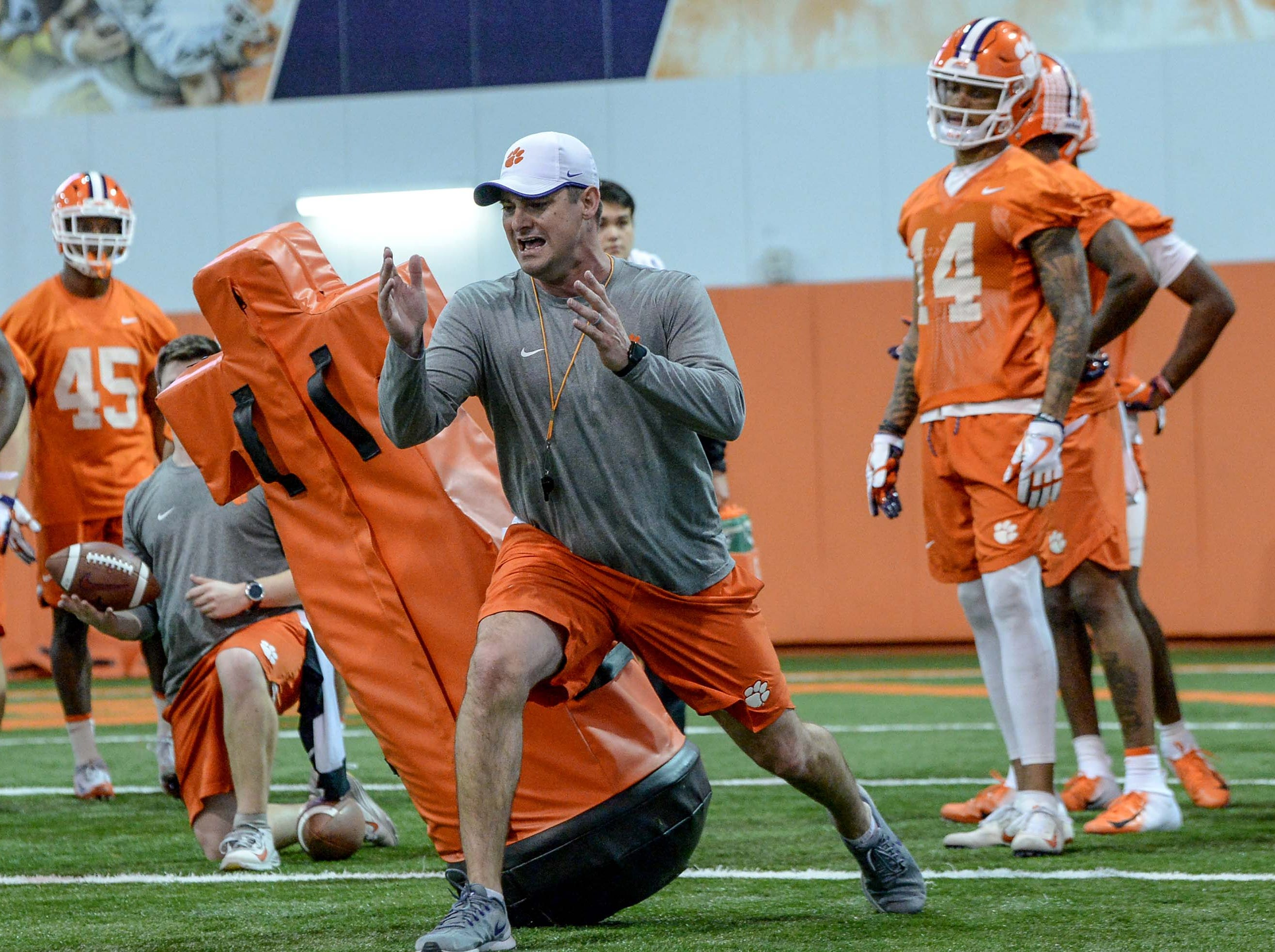 Clemson wide receiver coach Jeff Scott shows how to run through a drill during practice at the Poe Indoor Facility in Clemson Friday.