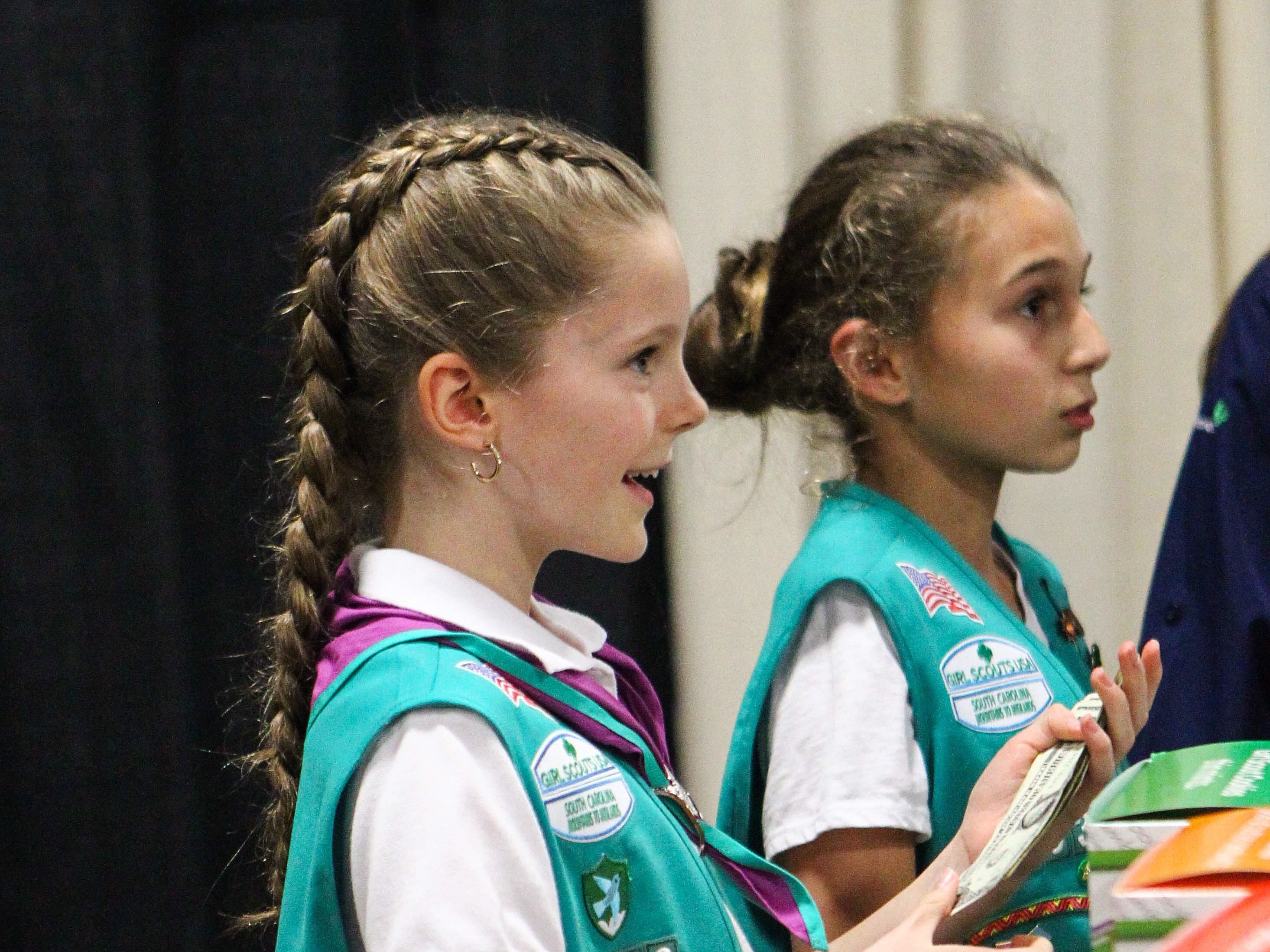 """Kelli Kivett, 10, and Leah Tysinger, 11, talk to customers at the Southern Home and Garden Show at the Greenville Convention Center on Friday, March 1, 2019. The Girl Scouts teach many life skills to young girls including """"financial literacy"""" Kelli's mother, Dee Kivett, said."""