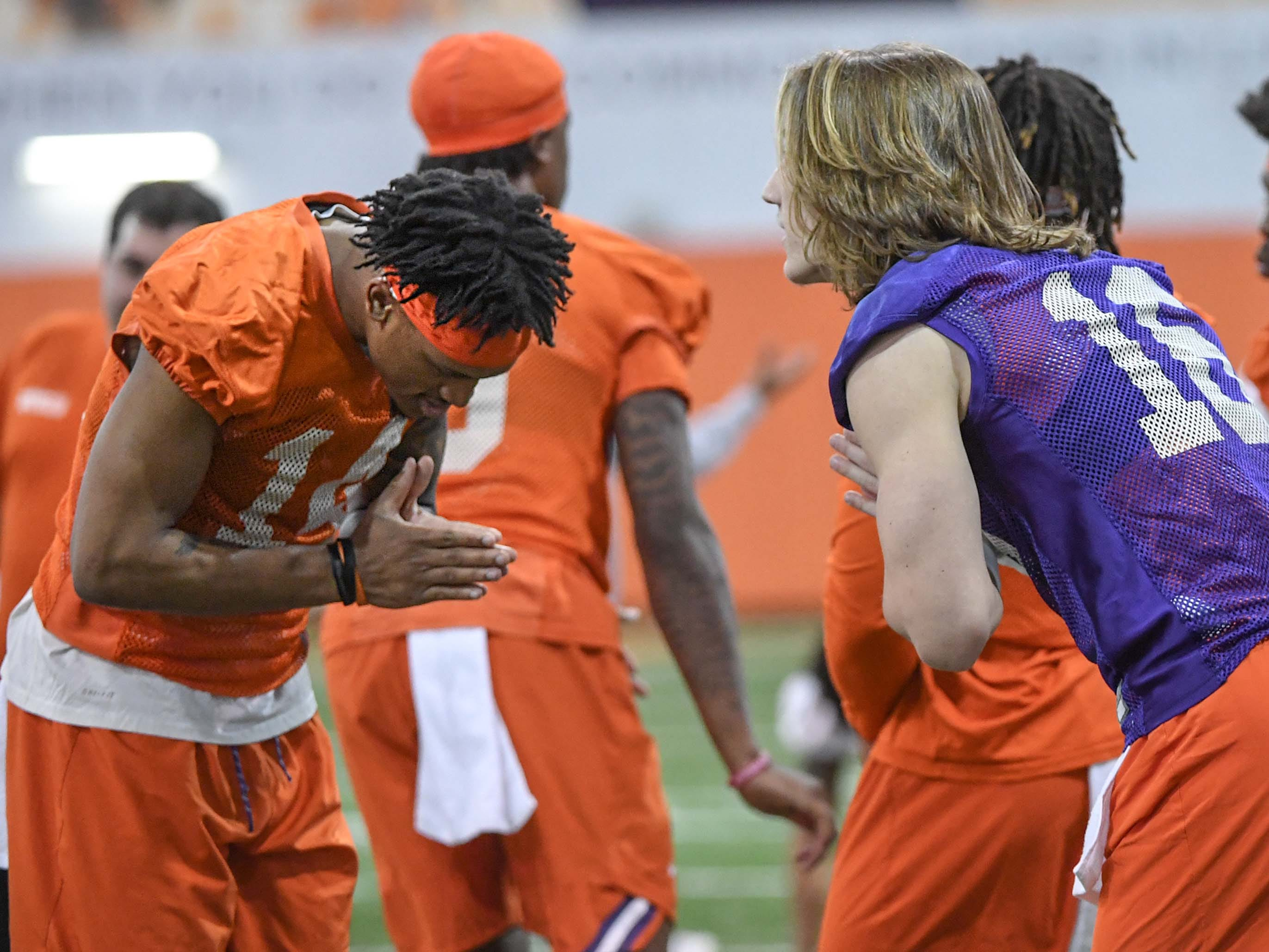 Clemson wide receiver Diondre Overton (14) and quarterback Trevor Lawrence (16) greet each other during practice at the Poe Indoor Facility in Clemson Friday.