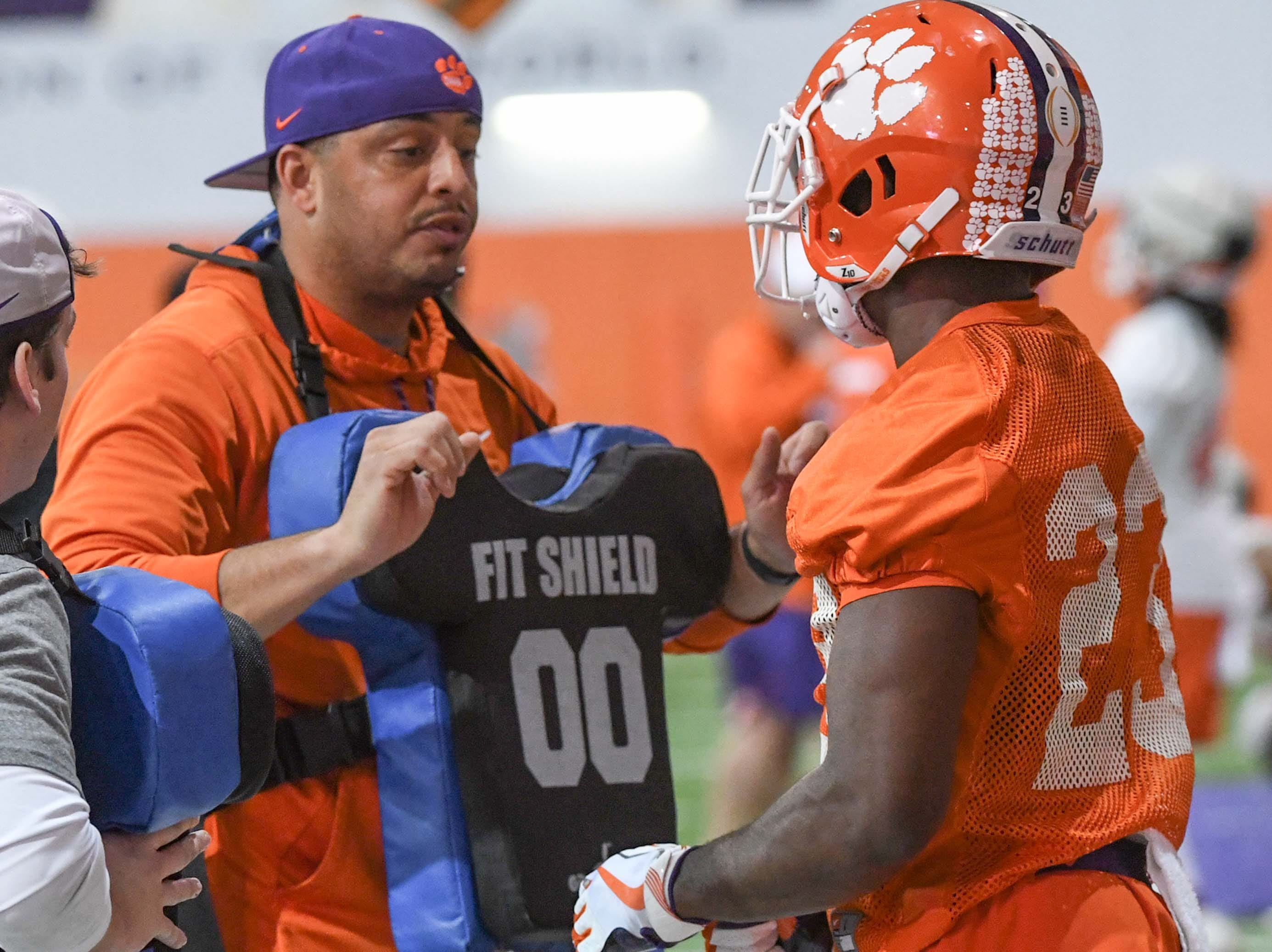 Clemson co-offensive coordinator Tony Elliott runs a drill with running back Lyn-J Dixon (23) during practice at the Poe Indoor Facility in Clemson Friday.