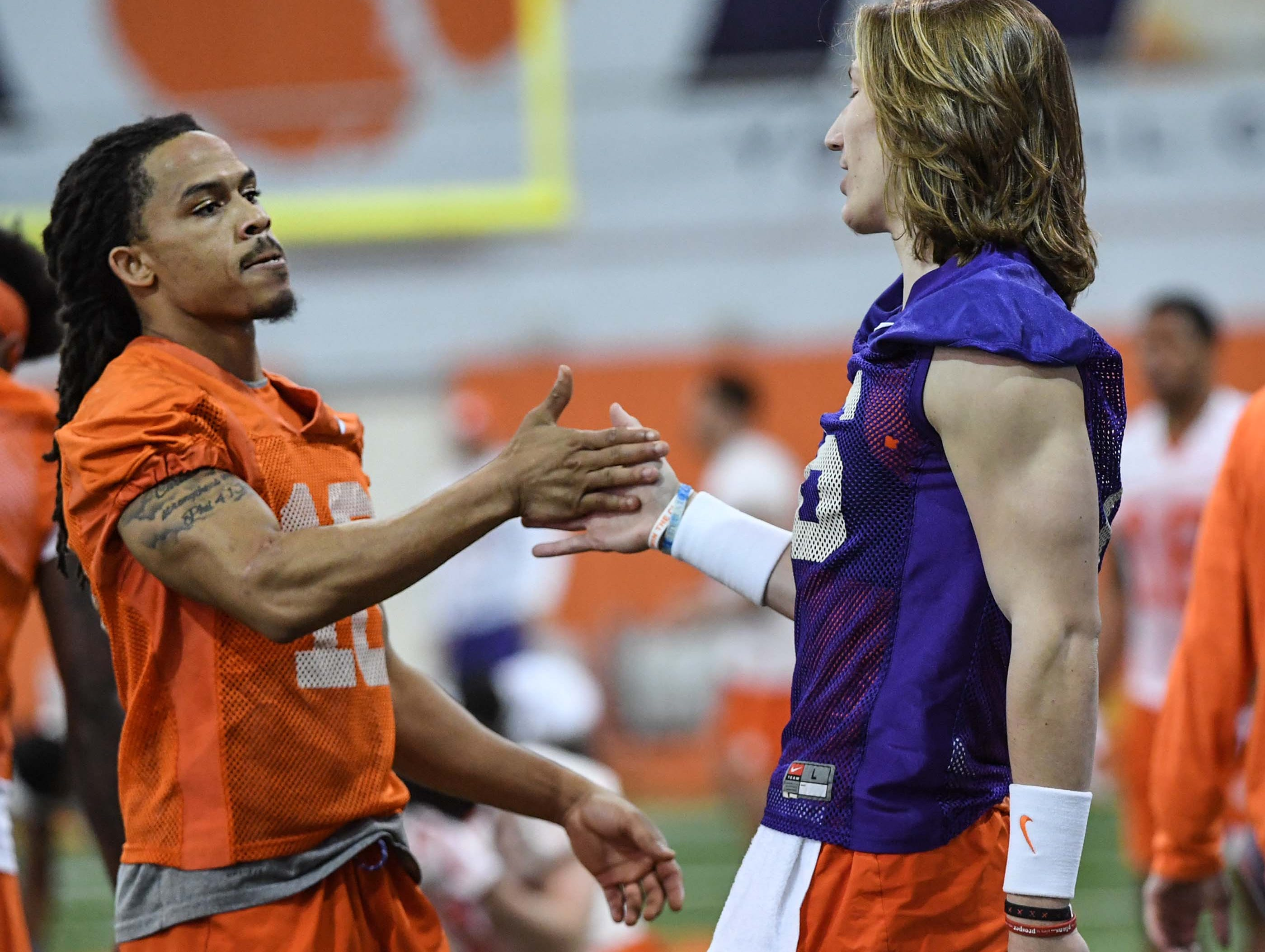 Clemson wide receiver T.J. Chase (18) and quarterback Trevor Lawrence (16) greet each other during practice at the Poe Indoor Facility in Clemson Friday.