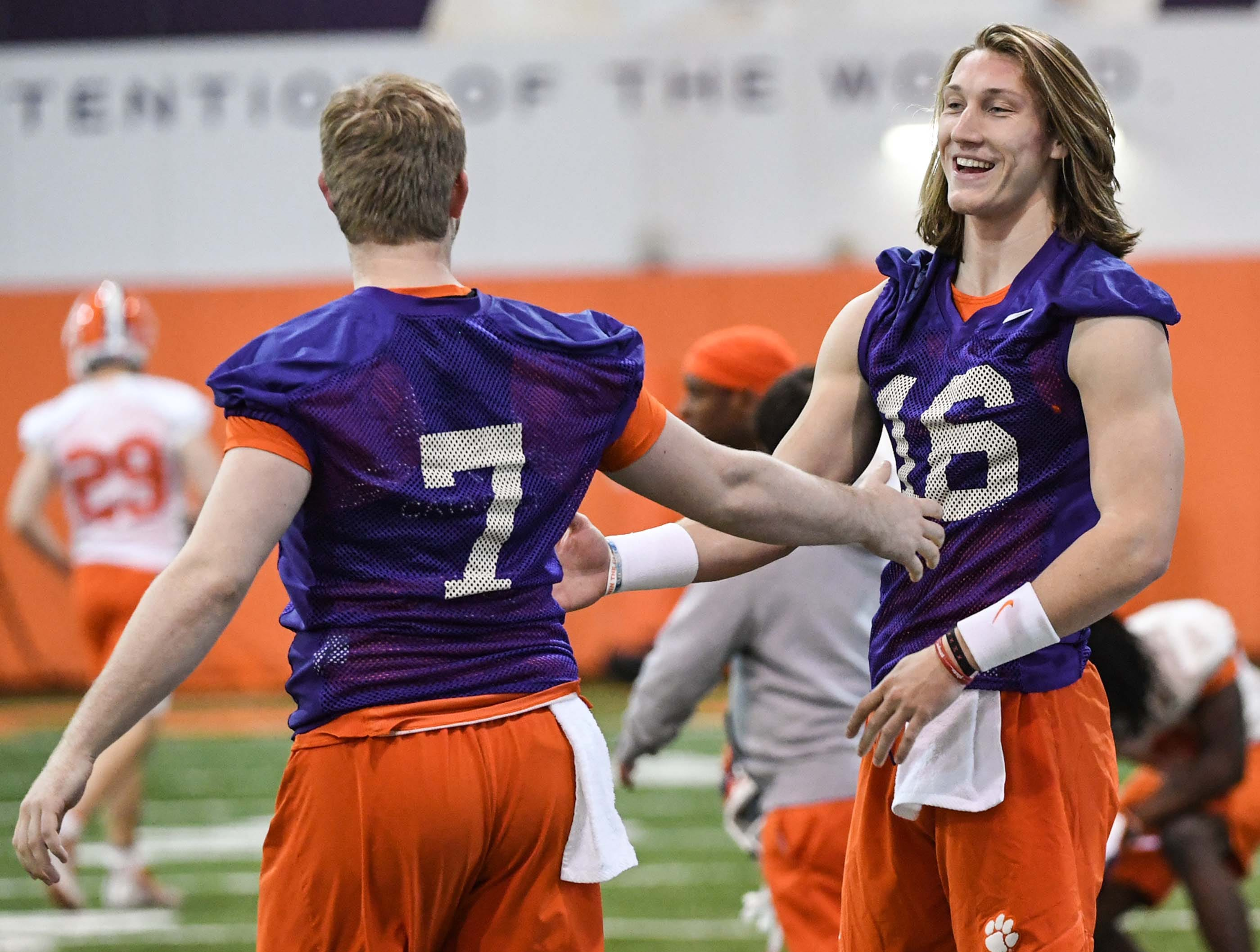 Clemson quarterback Chase Brice (7) and quarterback Trevor Lawrence (16) greet each other during practice at the Poe Indoor Facility in Clemson Friday.