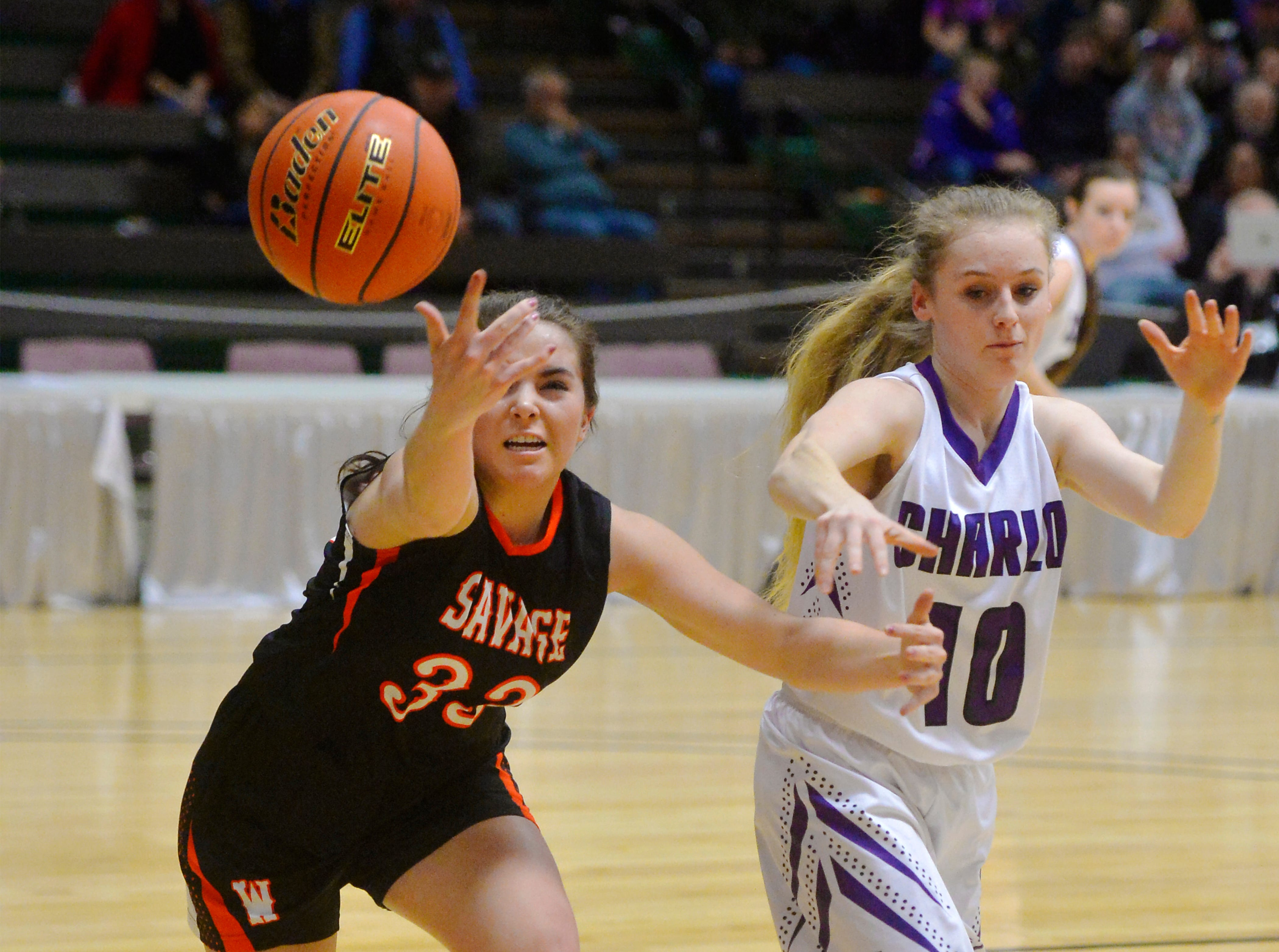 Savage's Kiana Miller attempts to steal the ball from Charlo's Kaitlin Cox during the Girls State C Basketball Tournament on Thursday in the Four Seasons Arena.
