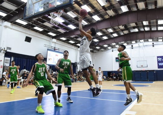 Saint Paul Warriors player Reo Aiken (23) scores on a drive against the John F. Kennedy Islanders during their IIAAG Boys' Basketball game at the Saint Paul Gym, March 1, 2019. The Warriors held off the Islanders 62-48.