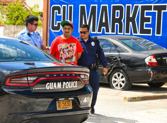 Guam Police Department officers escort a man, restrained in handcuffs, to an awaiting police cruiser after responding to a call for assistance at the CU Market in Harmon on Friday, March 1, 2019.