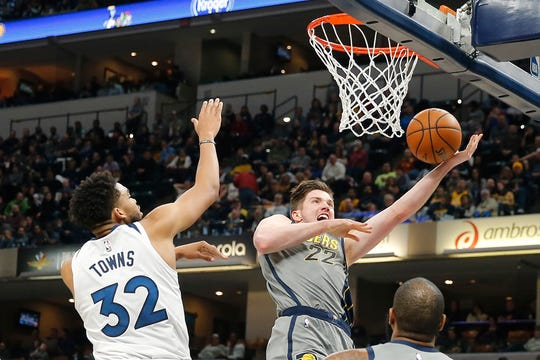 Feb 28, 2019; Indianapolis, IN, USA; Indiana Pacers forward TJ Leaf (22) shoots the ball past Minnesota Timberwolves center Karl-Anthony Towns (32) during the third quarter at Bankers Life Fieldhouse.