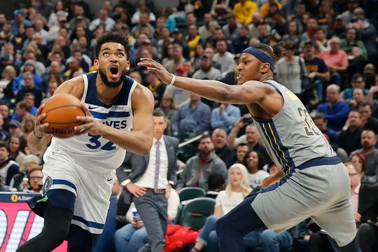 Feb 28, 2019; Indianapolis, IN, USA; Minnesota Timberwolves center Karl-Anthony Towns (32) prepares to shoot the ball past Indiana Pacers center Myles Turner (33) during the first quarter at Bankers Life Fieldhouse.