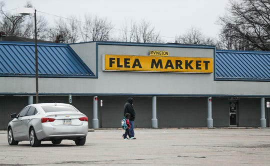 An adult and child walk past the Irvington Flea Market in Irvington Plaza, 6243 East Washington Street, Indianapolis Ind. on Tuesday, Feb. 19, 2019.