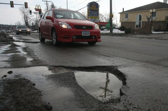 A vehicle approaches a large pothole along 1st Avenue , Sunday March 9, 2008, in Coralville, Iowa.