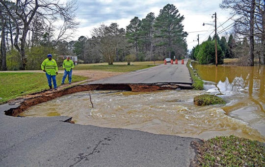In this Tuesday, Feb. 26, 2019 photo, city workers assess damage caused by flooding on Plymouth Road in Columbus, Miss.
