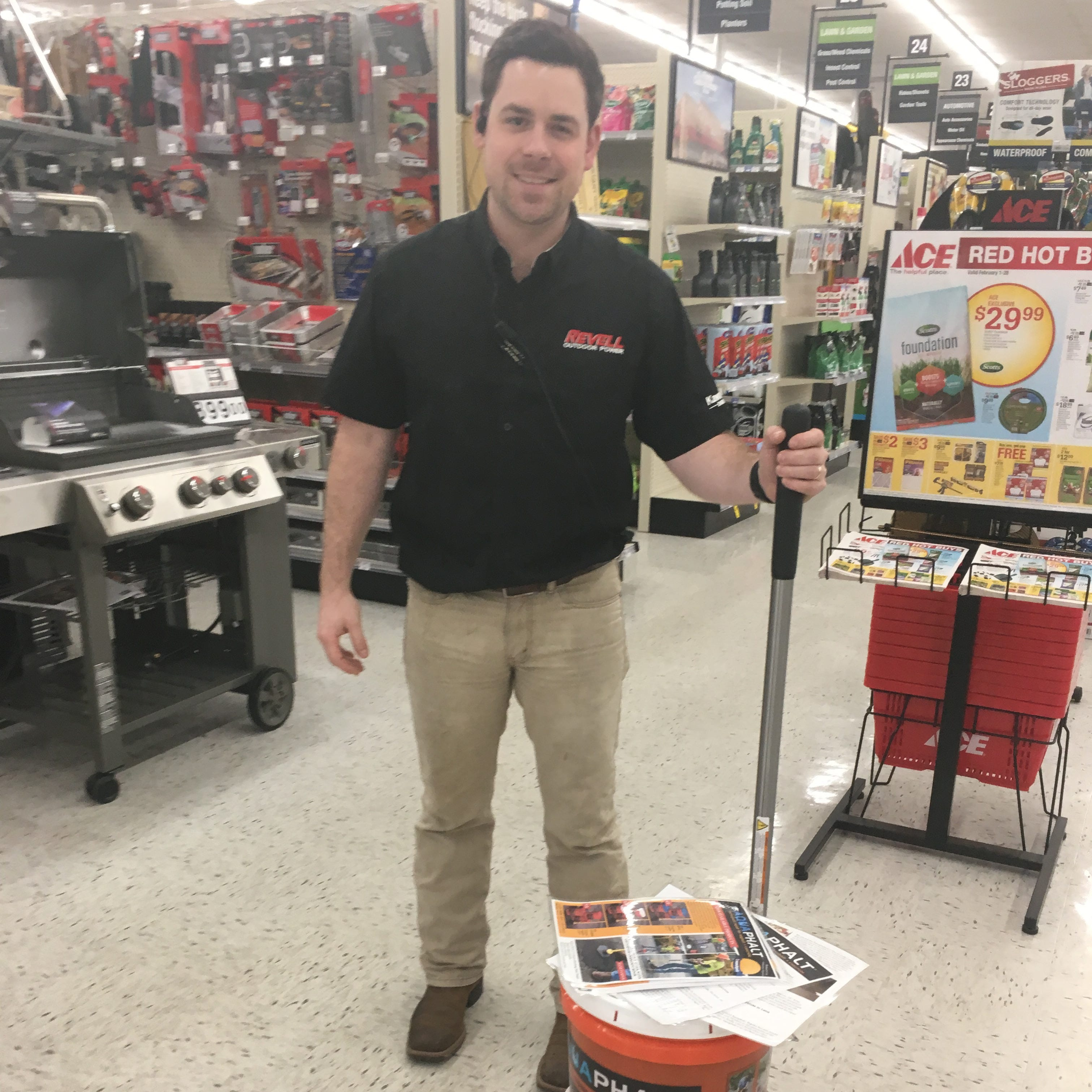 Reville Ace Hardware store manager Paxton Rooks stands next to an Aquaphalt display at the Jackson store on Feb. 28, 2019.