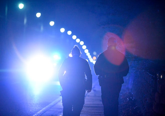 Jackson police officers search between homes after a short pursuit while trying to serve a warrant at North Highland and Arlington, in Jackson, Tenn., on Friday, March 1, 2019.